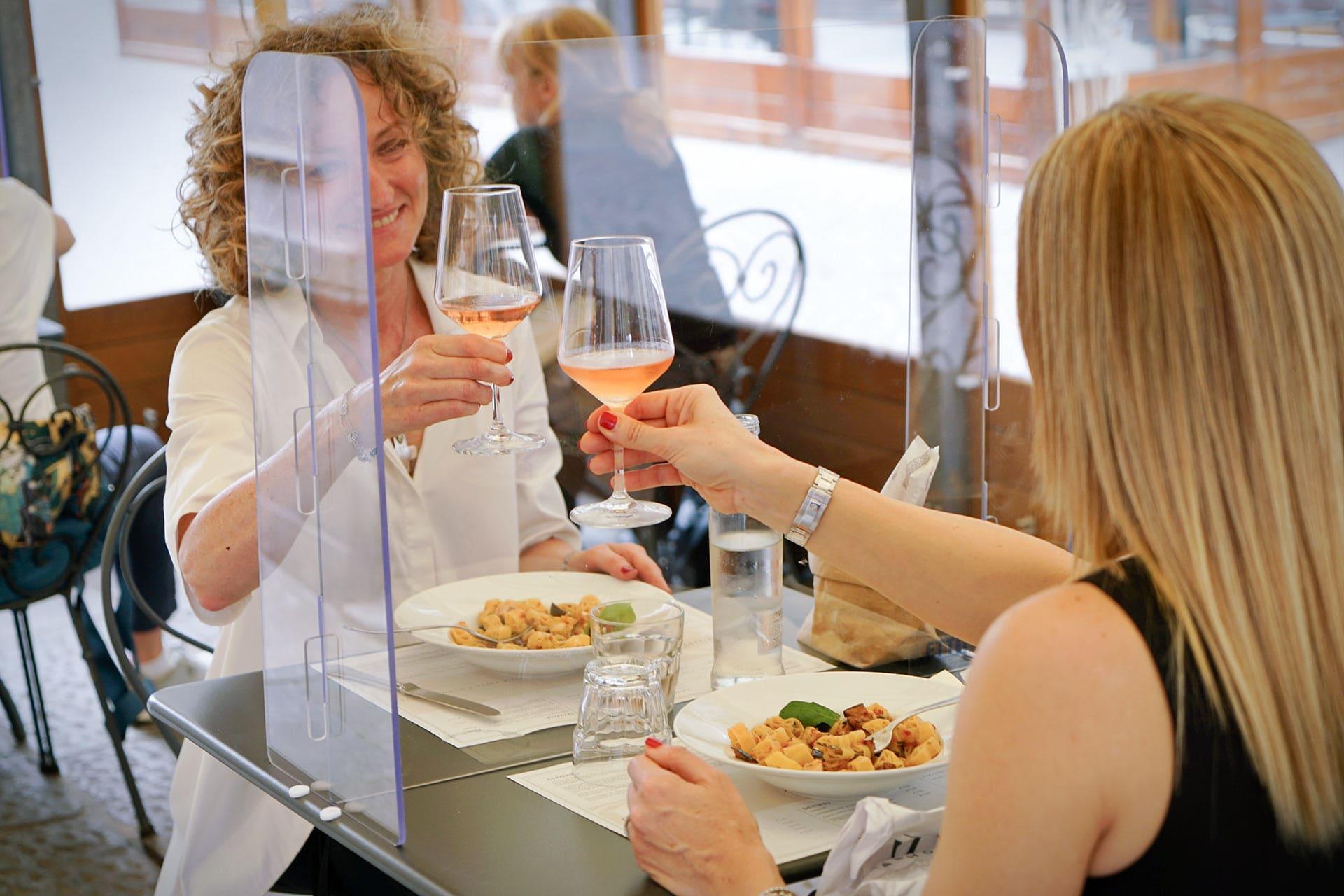 Una coppia di donne brinda da dietro al plexiglass