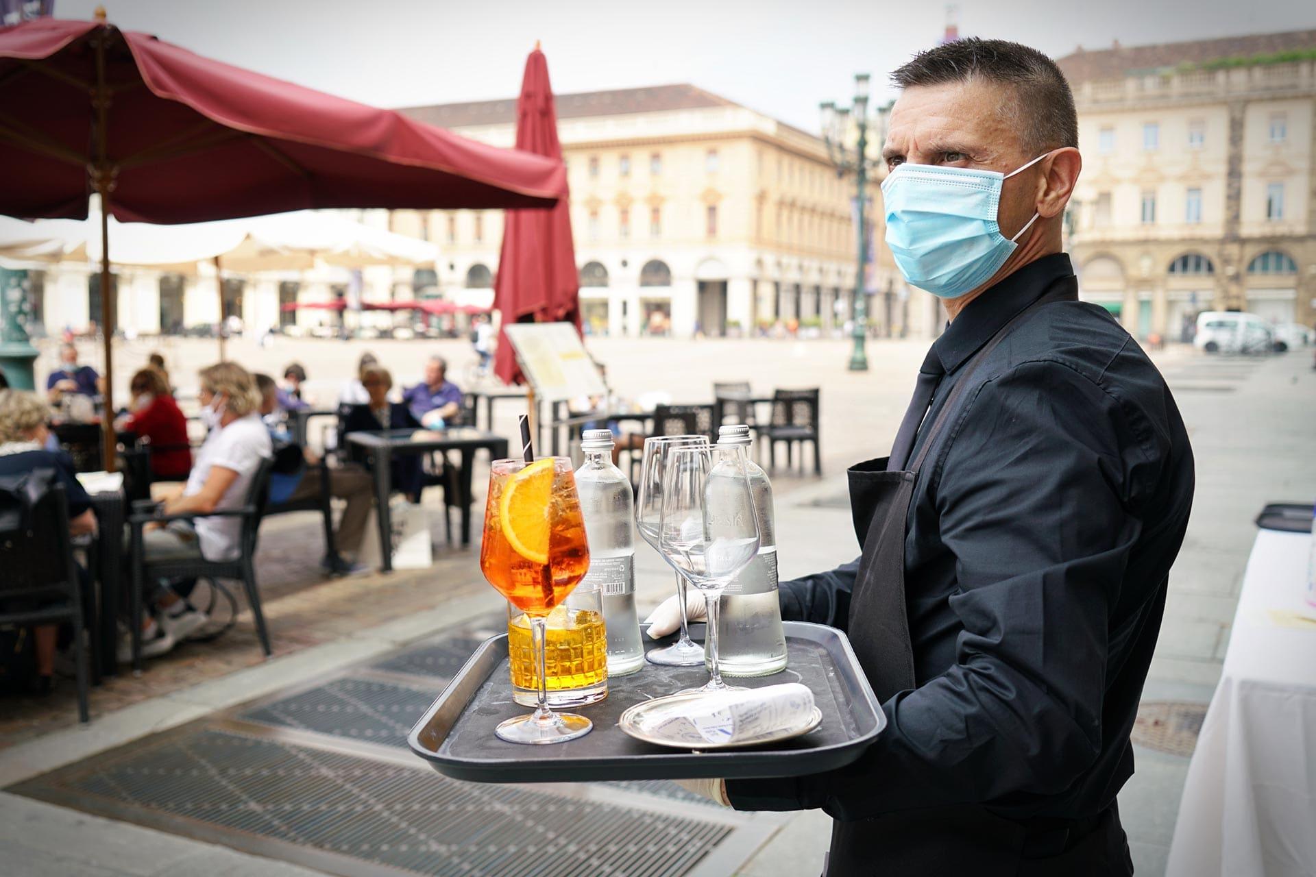 Cameriere con la mascherina e un vassoio pieno di bibite