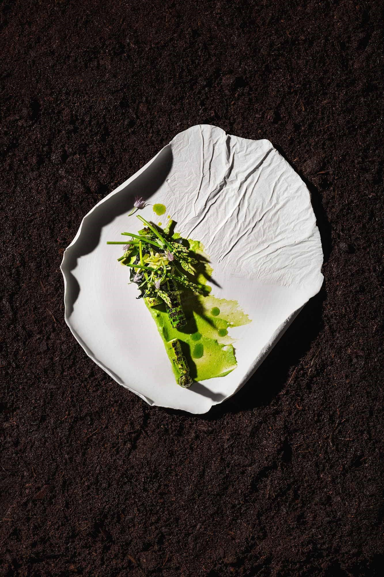 Burnt green asparagus served on a leaves plate by Aino Nebel